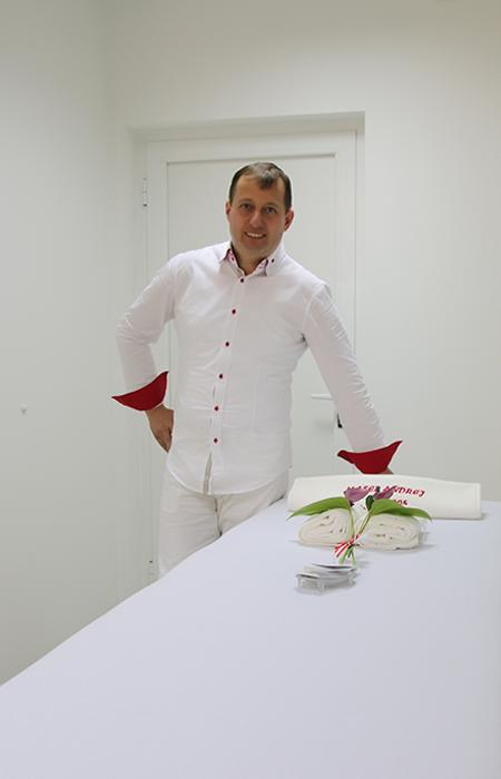 Fotografija maserja Andreja Uleta naslonjenega na masažno mizo.